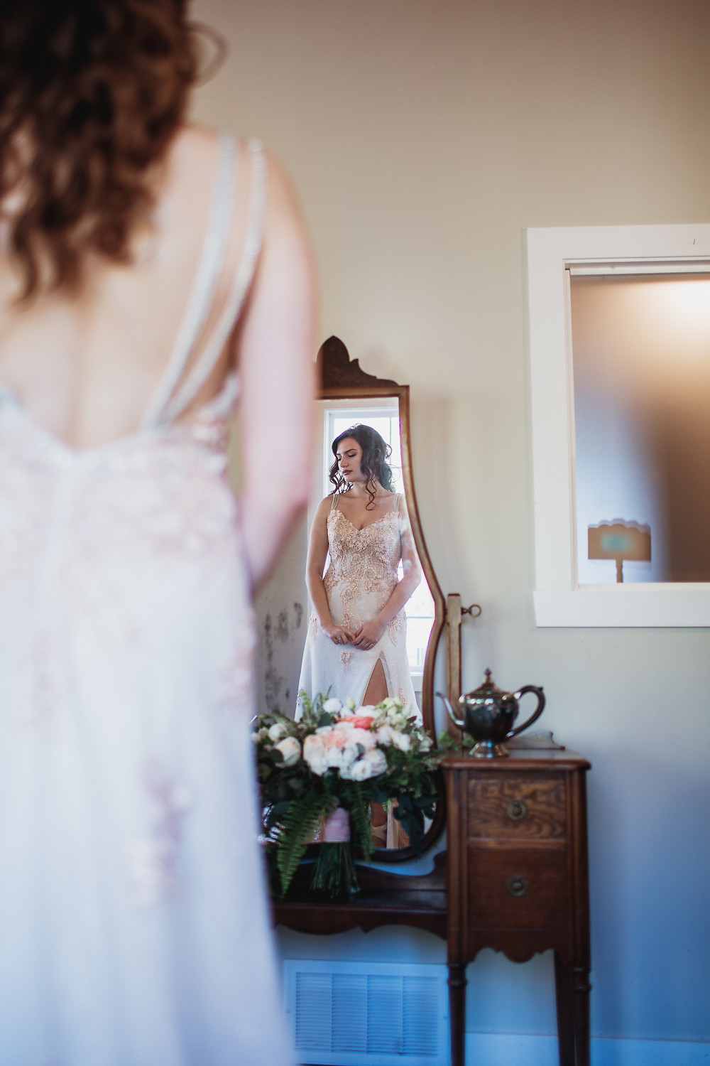 Bride getting ready in front of mirror.