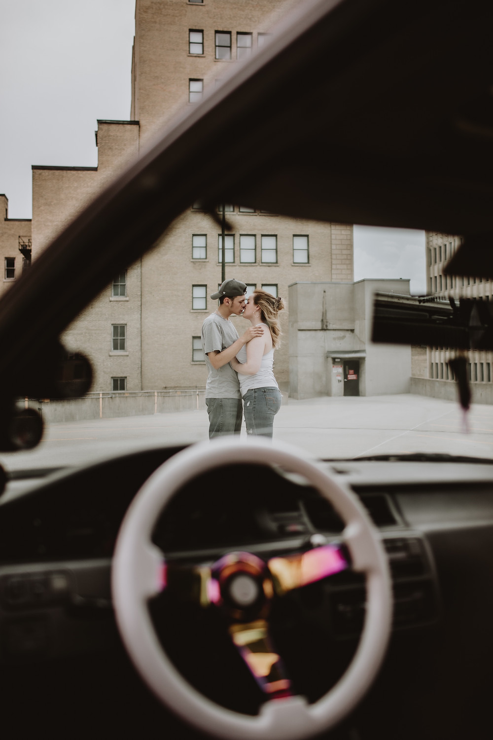 You couple kisses, framed by the front windshield of their car.