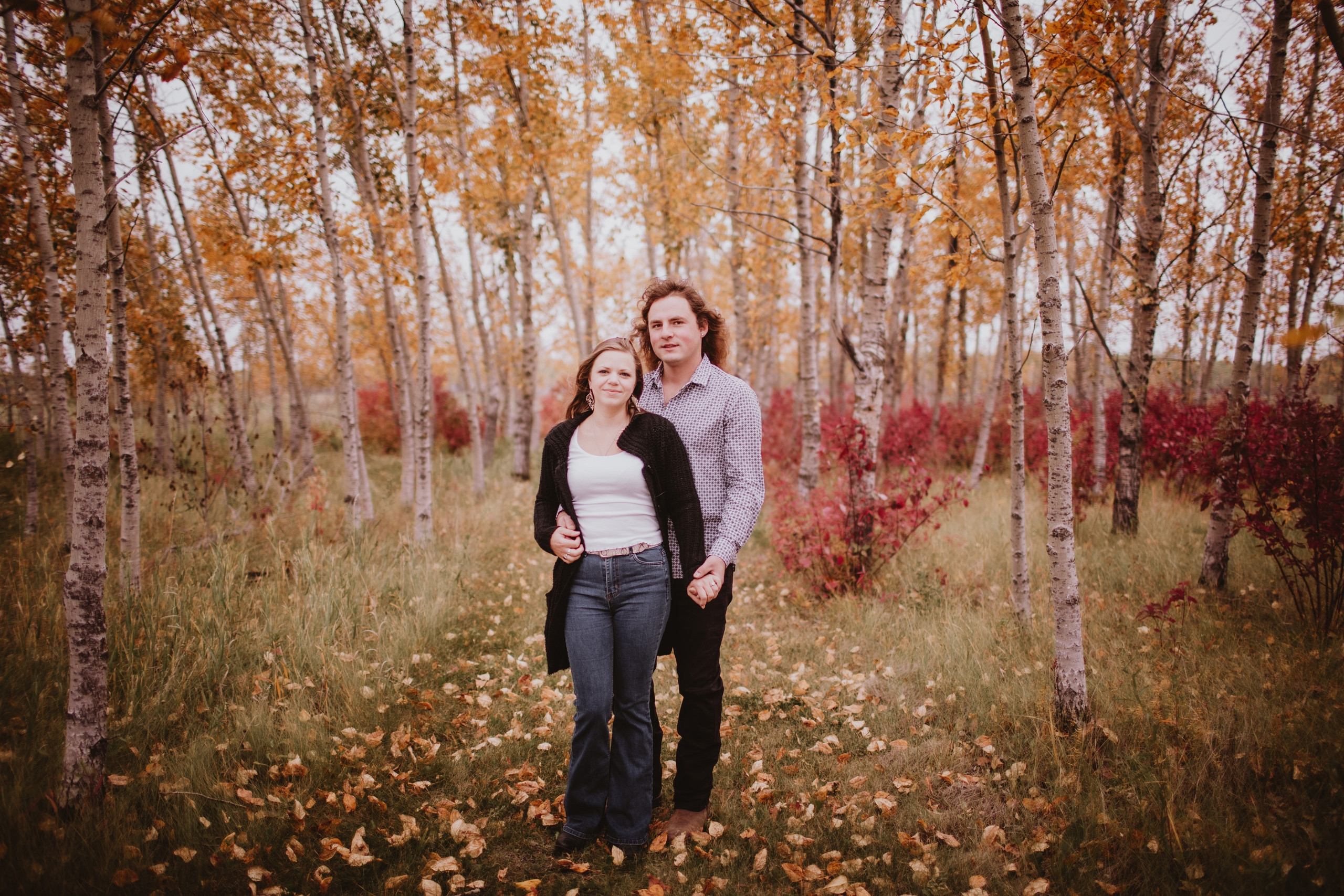 Couple Poses in Forest during fall engagement session.