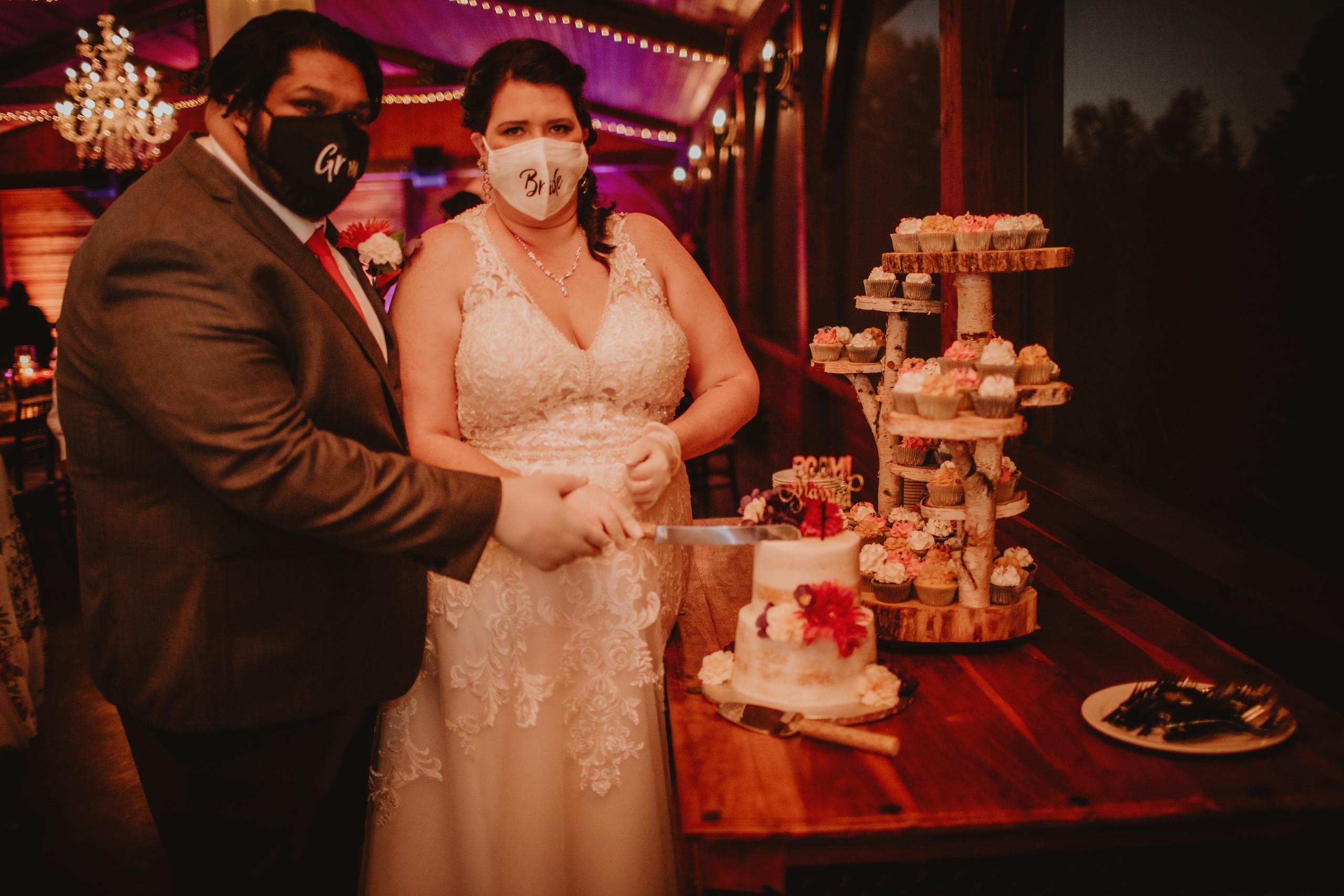 Wedding Couple Cuts Cake during wedding reception at Rivers Edge Resort.