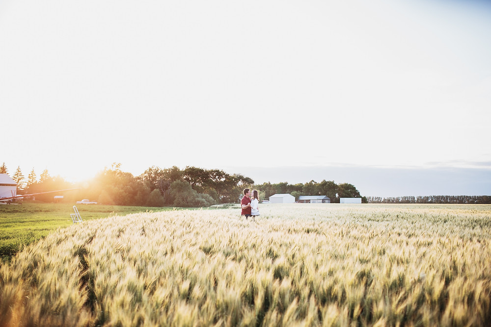Couple poses in their wheat field for engagement photoshoot.