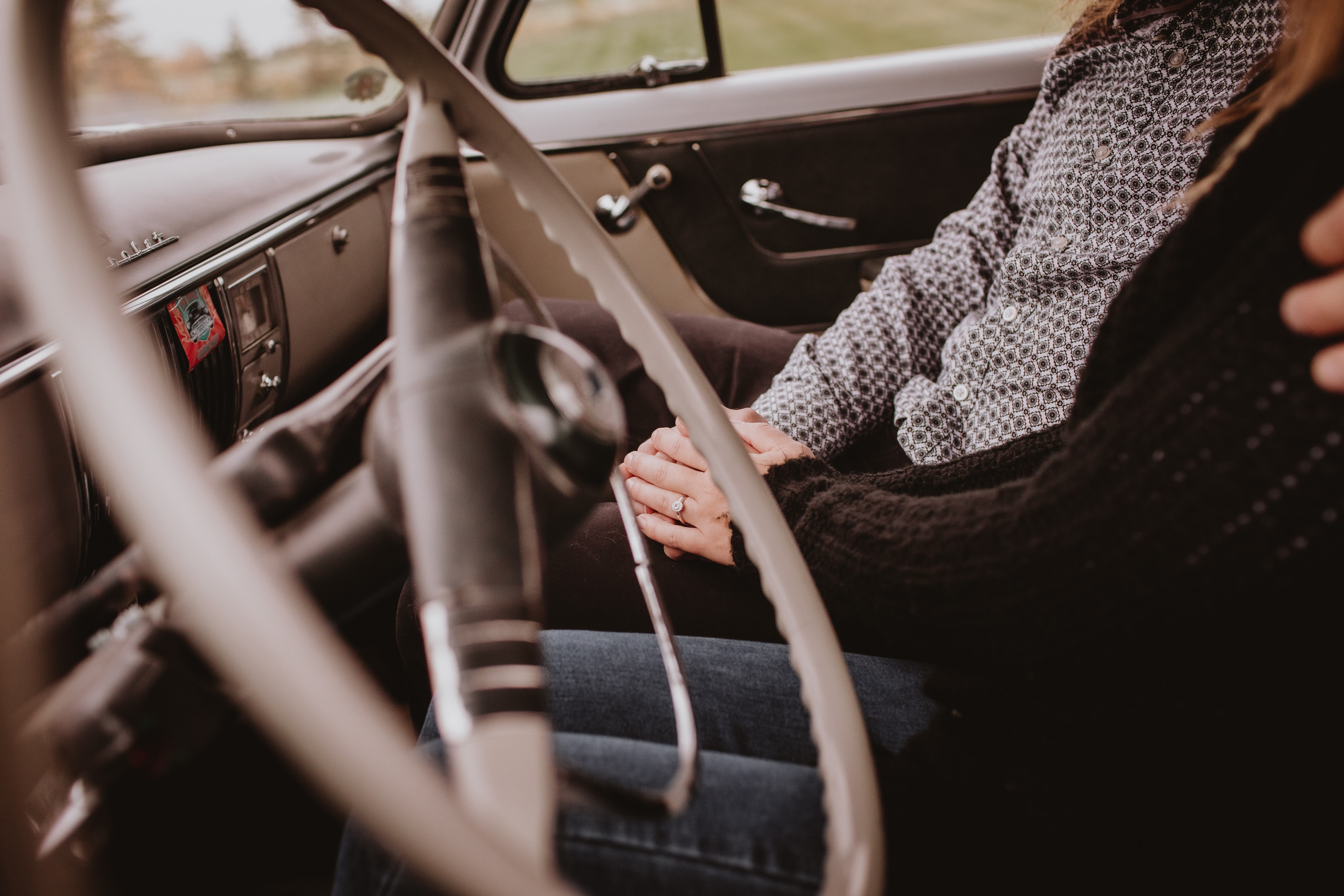 Couple's Engagement Ring seen as they sit in their restored vintage car.