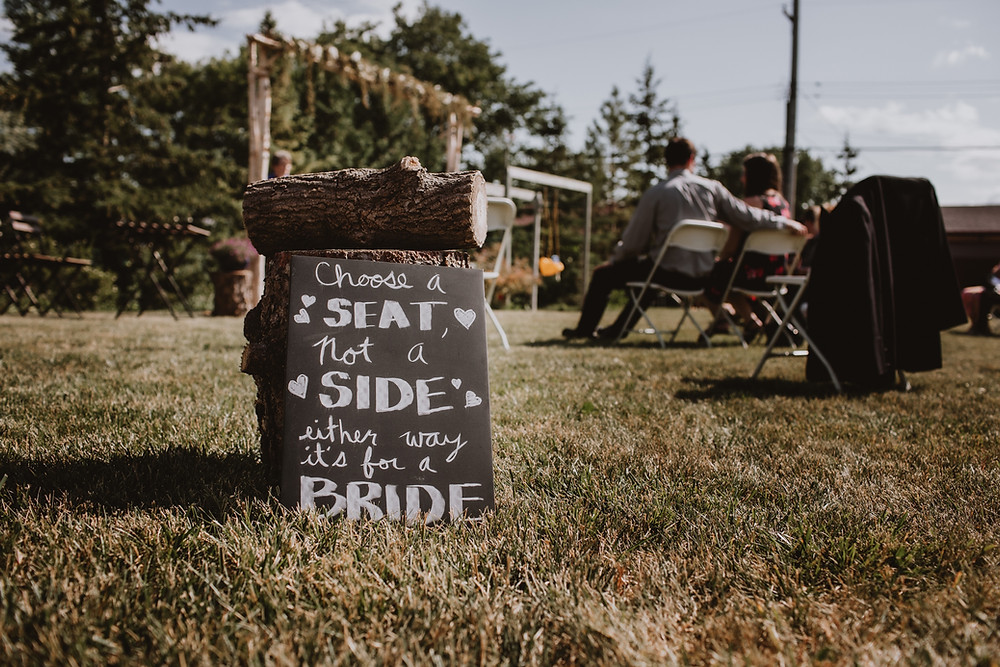 "Sign ""Choose a seat, not a side; either way it's for a bride"""