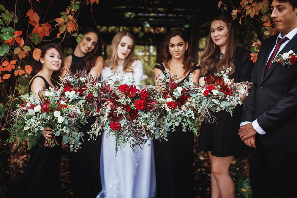Red bouquets with hearty greens, fall wedding inspiration.