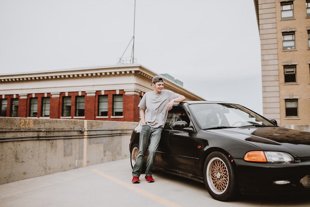 Graduate showing of his black Honda Civic.