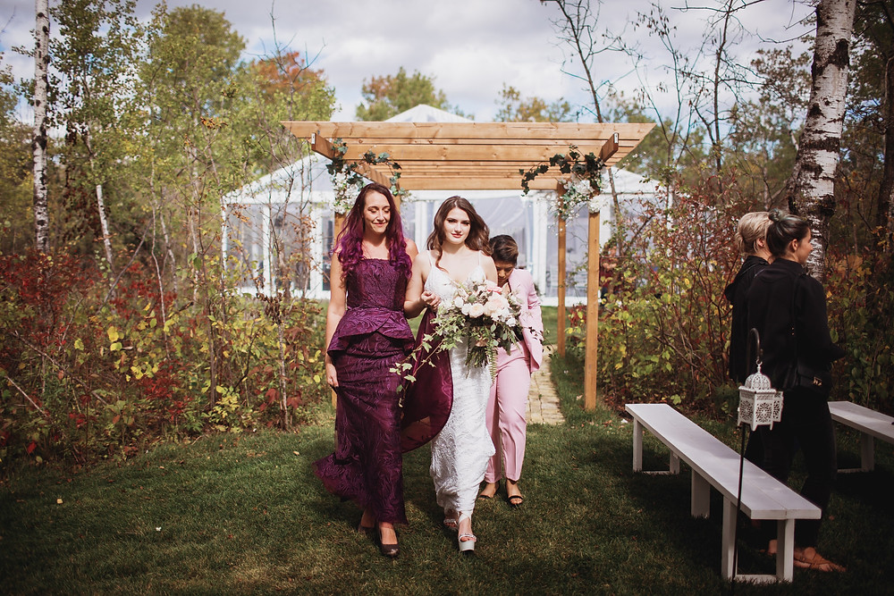 Bride walks down aisle with mother of bride wearing eggplant gown by Anna Lang Bridal