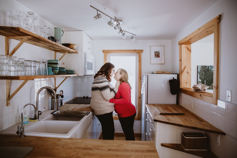 Couple cuddling in kitchen during in-home engagement photo shoot.