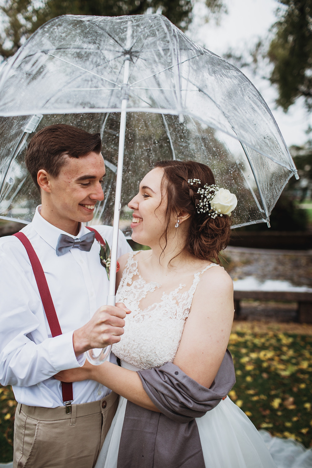 Smiling bride and groom under umbrella during rainy fall wedding day.