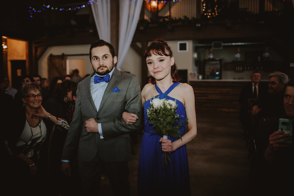 Bridesmaid and groomsman walk down aisle at indoor wedding ceremony.