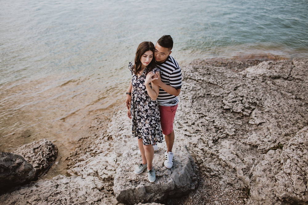 Engaged couple poses, backdropped by clear blue water.