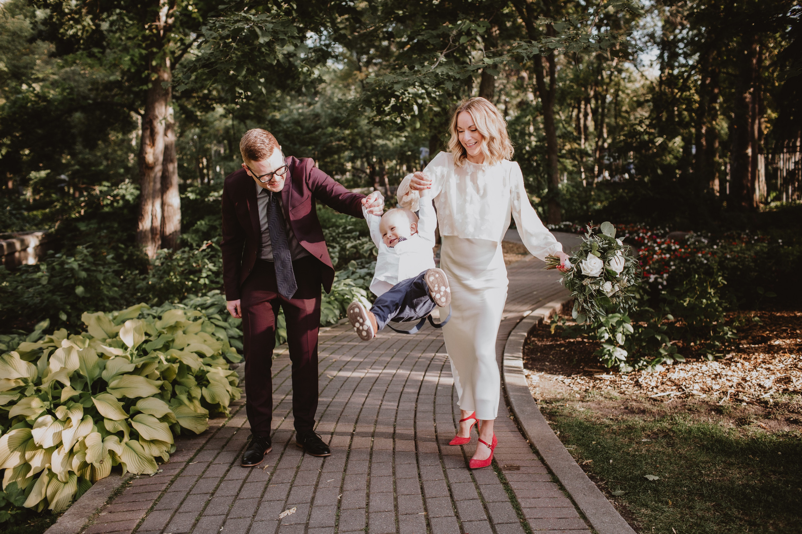 Family Wedding Ideas - bride and groom swing son between them, celebrating post wedding ceremony.
