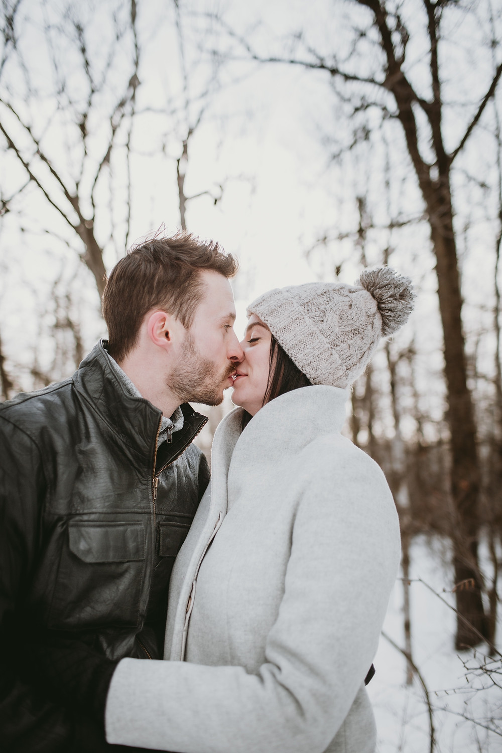 engaged couple kisses during snowy forest photo session.
