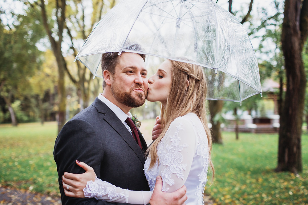 Bride kisses grooms cheek under a clear bubble umbrella in Clear Lake, Manitoba.