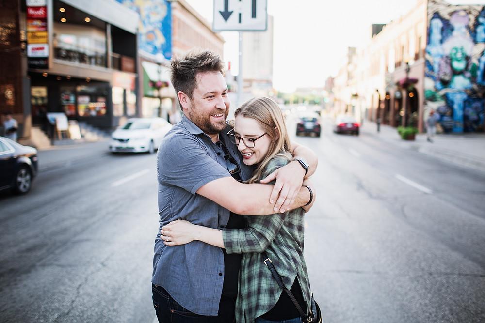 Engaged couple embraces, backdropped by Osborne Street.