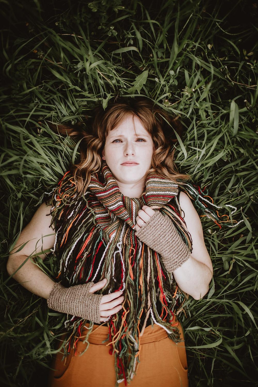 Fibre artist lays in grassy field, showcasing her handknit, wool creations.