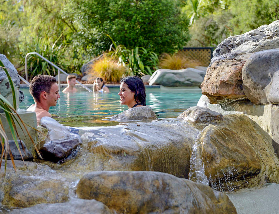 Boulders and water cascade at edge of natural hot pool landscape design