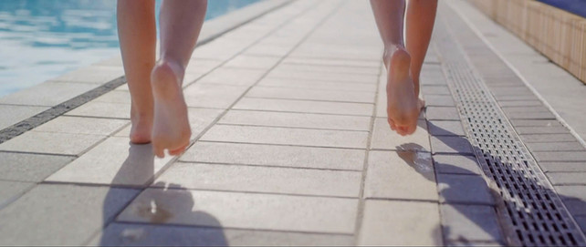 Bare feet walking over the paved landscape design at New Brighton Hot Pools