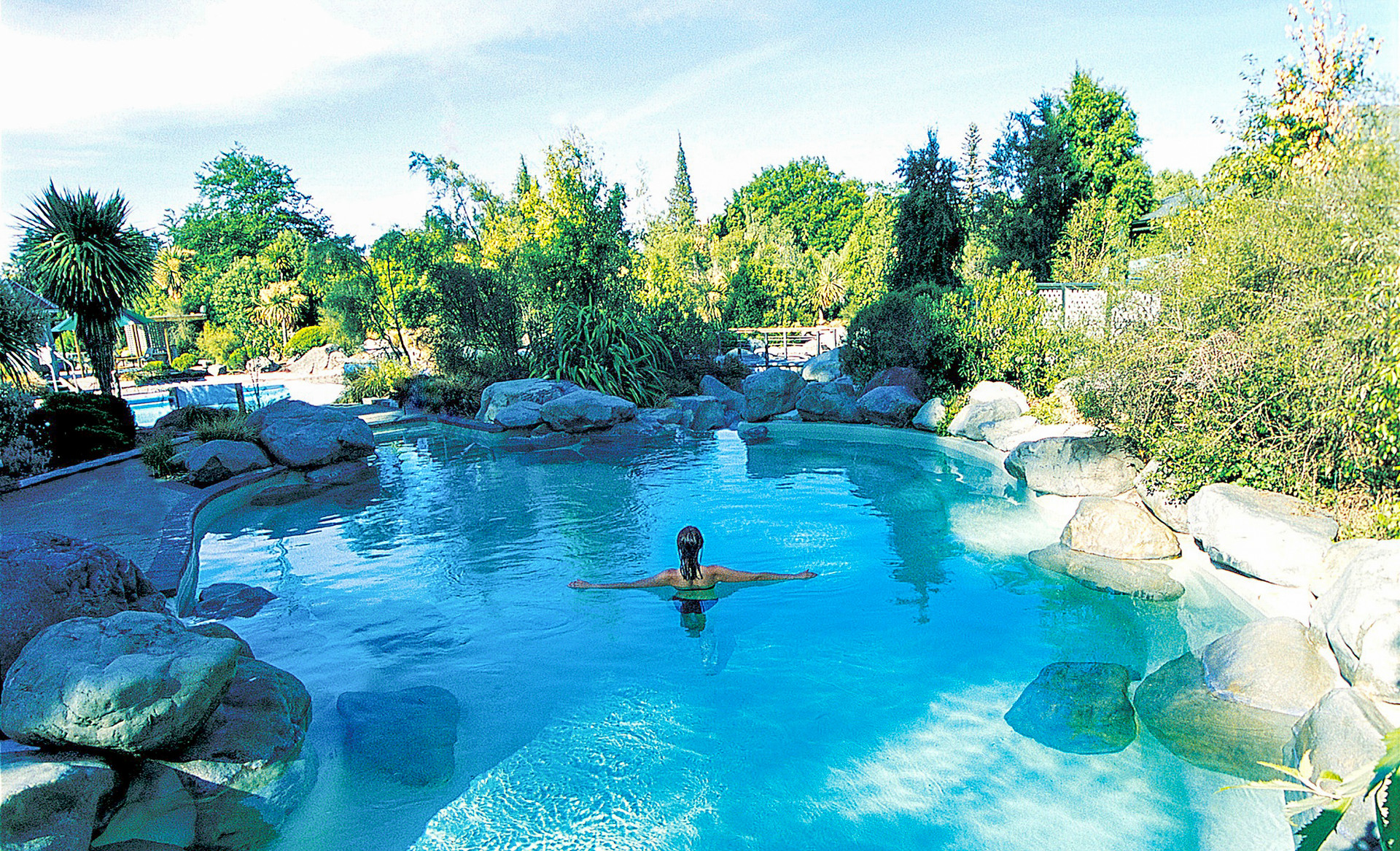 bather relaxing in natural hot pool landscape design at hanmer springs