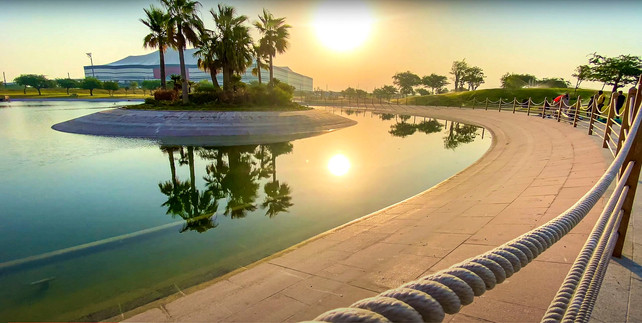 Sunset over a landscape architecturally designed lake at Al Bayt FIFA 2022 World Cup Stadium