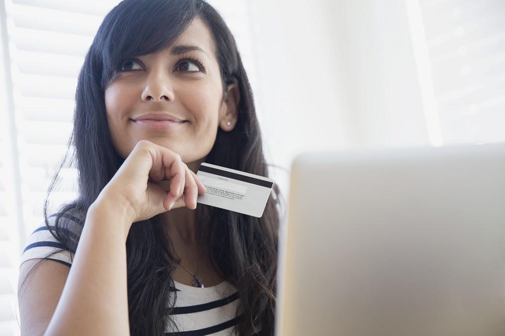 Mujer joven contemplando compras por internet