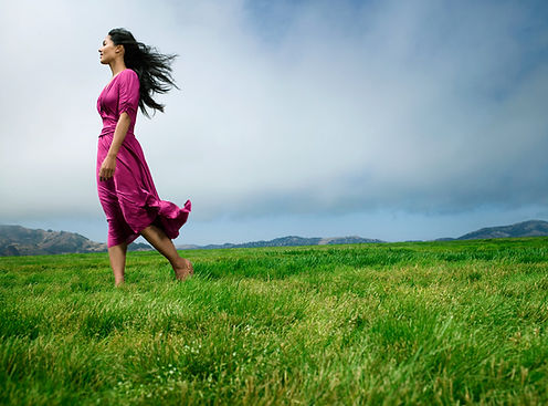 A Latina woman walking in the grass wearing a pink dress.