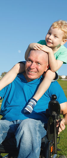 A son rides on his fathers shoulders. His father uses a wheelchair.