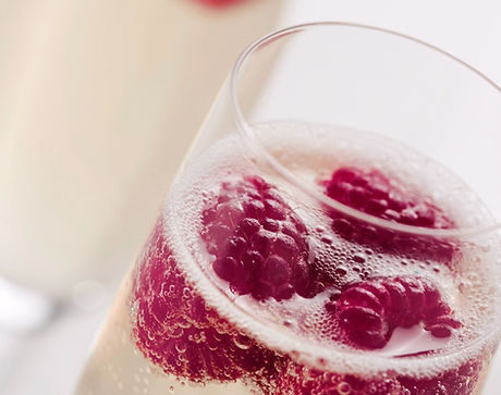 an elegant flute of Champagne with fresh ripe raspberries inside