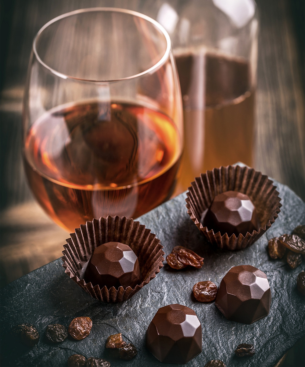 A glass of port wine, chocolate ganaches and raisins for tasting and enjoyment