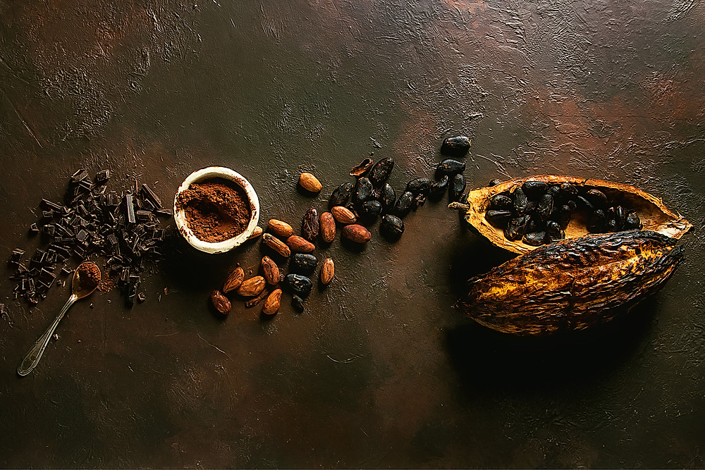Shaved chocolate, cocoa powder & cocoa beans beside a cocoa pod.