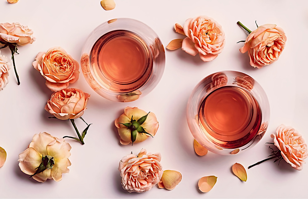 Two glasses of Rose Wine surrounded by pink roses and rose petals on a pink background.