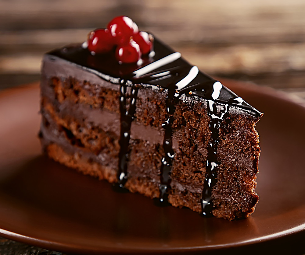 Rich and moist chocolate cake with thick chocolate sauce drizzled over it.