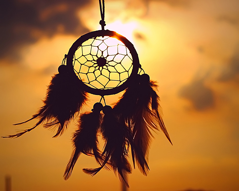 Native Indian or First Nations Dream Catcher hanging in the late evening sunshine.
