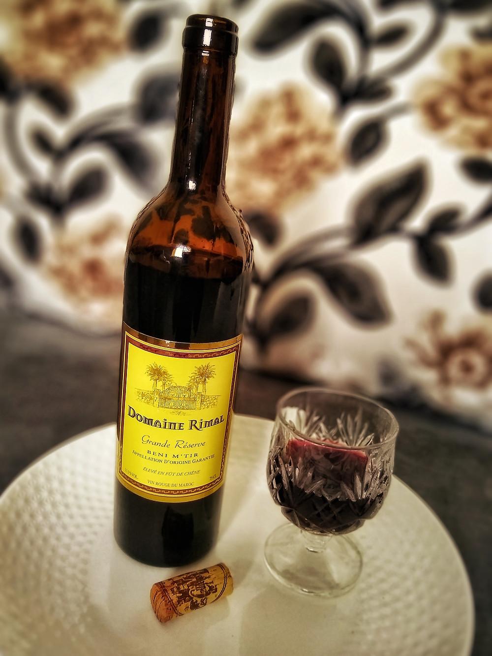 Open bottle of Les Celliers de Meknès Domaine Rimal Grande Réserve wine with a filled wine glass and cork