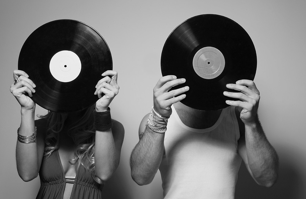 Two people with their faces hidden by vinyl records