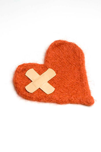 Orange fabric heart with criss crossed bandaids on it.