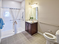 A bathroom within a furnished model apartment