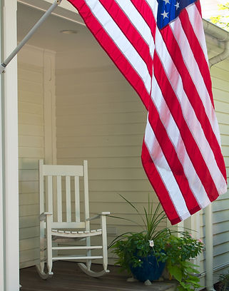 A photo of an America Flag hanging in front of a porch with a rocking chair