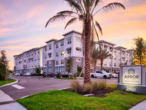 A beautiful exterior view of Arbor Village with a sunset filling the sky
