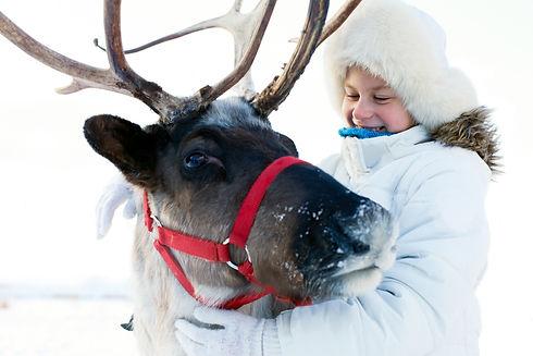 Happy little girl hugging her reindeer.