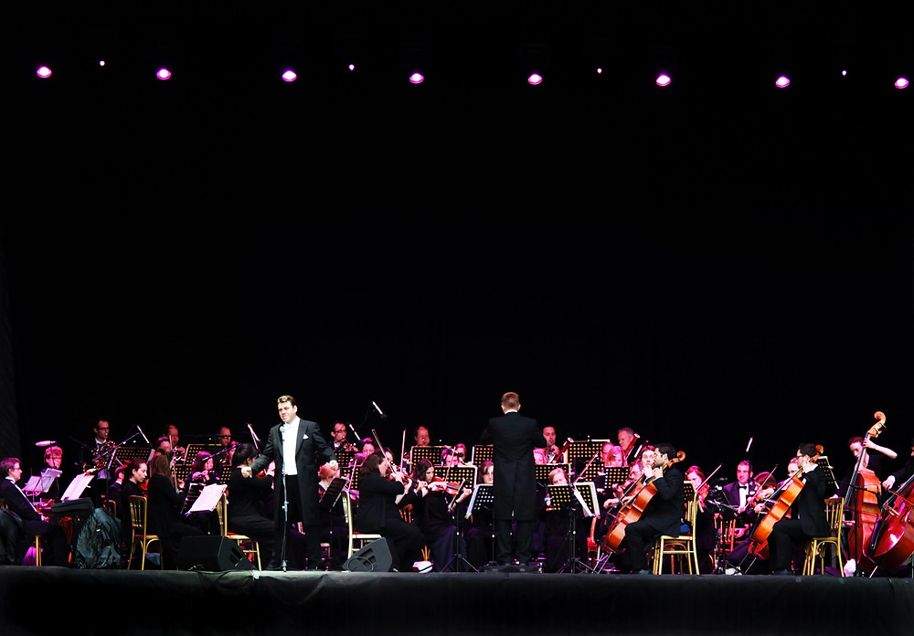 Tenor singer, Lee Bradley performing in front of an orchestra on stage