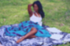 Olivia Corvisart in a blue skirt and white shirt laying on a blanket on green grass.