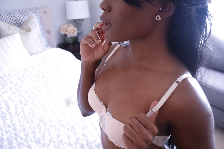 Olivia Corvisart in a pink bra standing next to a white bed