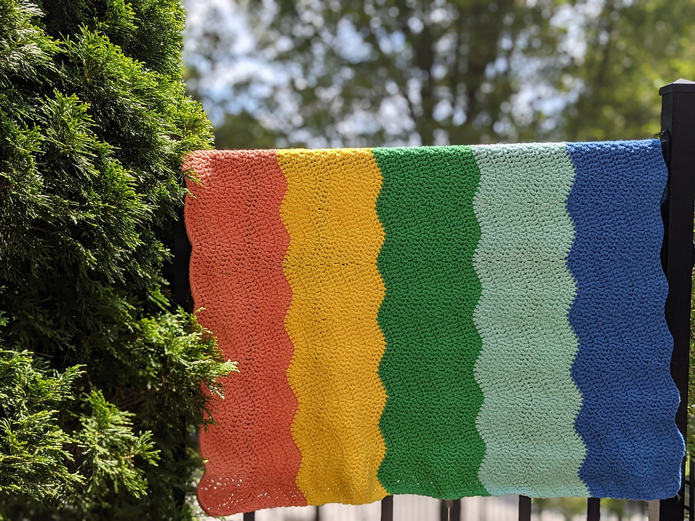 A navy crochet blanket made with a crossed cluster stitch pattern and bordered in white. The blanket is draped over a chair in front of a cypress tree.
