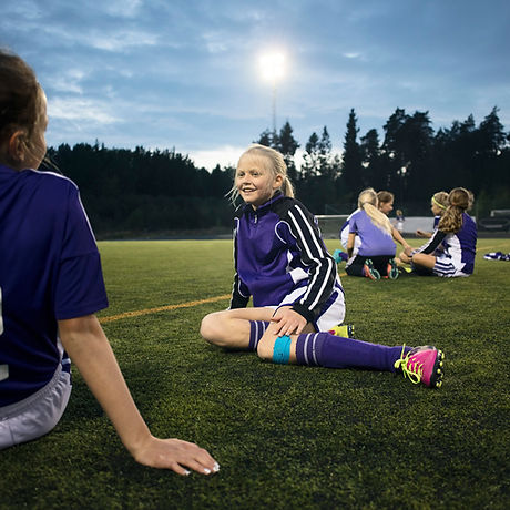 Girls Relaxing on Soccer Field