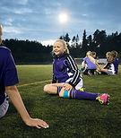 Meisjes ontspannen op voetbalveld