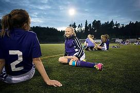 Mädchen, die auf Fußballplatz sich entsp