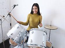 Teenage girls smiling while playing drum