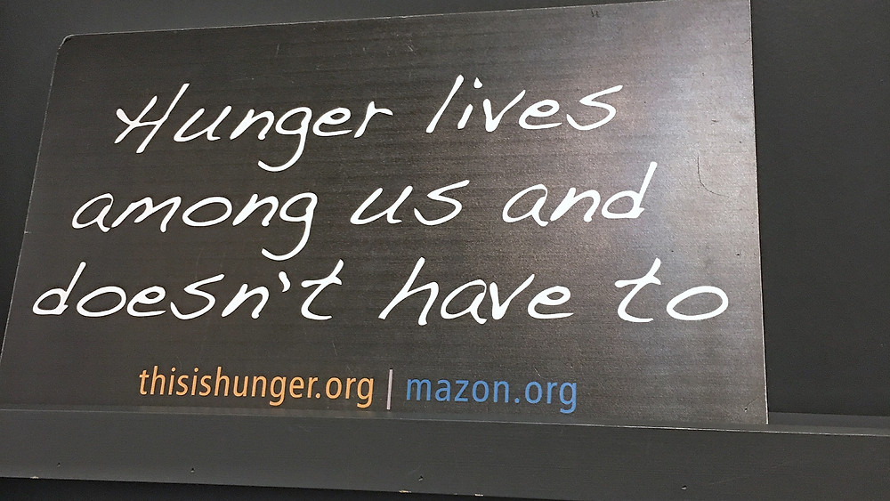 Sign says Hunger Lives Among Us and Doesn't Have To.
