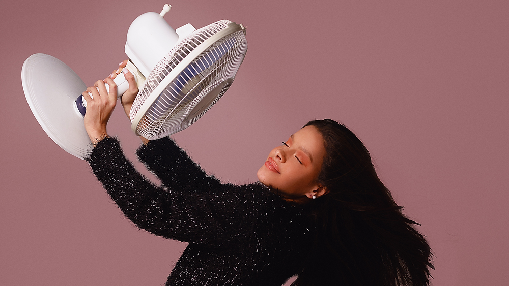 Woman with fan. Start of menopause can mean hot flashes