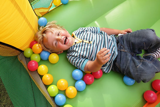 A child playing in a bounce house representing the happy, young patients of tinnitus treatment center High Level Speech & Hearing Center in New Orleans, LA